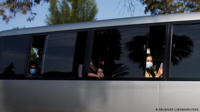Afrika Uganda: Menschen mit Atemschutzmasken blicken aus einem Bus mit getönten Scheiben.