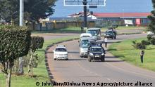 (210826) -- ENTEBBE, Aug. 26, 2021 (Xinhua) -- Vehicles ferry Afghan evacuees from Entebbe International Airport to a hotel in Entebbe, 40km south of Kampala, Uganda, Aug. 25, 2021. The first batch of evacuees from Afghanistan arrived in Uganda Wednesday morning, the country's Foreign Affairs Ministry said in a statement. A total of 51 evacuees, including men, women and children, arrived at the Entebbe International Airport on a privately chartered flight, before being escorted by local police to a hotel in Entebbe, 40 km south of the capital Kampala. (Photo by John Arry/Xinhua)