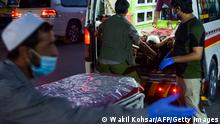 EDITORS NOTE: Graphic content / Medical staff bring an injured man to a hospital in an ambulance after two powerful explosions, which killed at least six people, outside the airport in Kabul on August 26, 2021. (Photo by Wakil KOHSAR / AFP) (Photo by WAKIL KOHSAR/AFP via Getty Images)