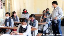 (210823) -- BANGALORE, Aug. 23, 2021 (Xinhua) -- Students of a government school attend a class on the first day of reopening for the 9th and 10th standards and the higher secondary classes, at 50-percent seating capacity, in Bangalore, India, on Aug. 23, 2021. These schools had been closed for 18 months due to the COVID-19 pandemic. (Str/Xinhua)