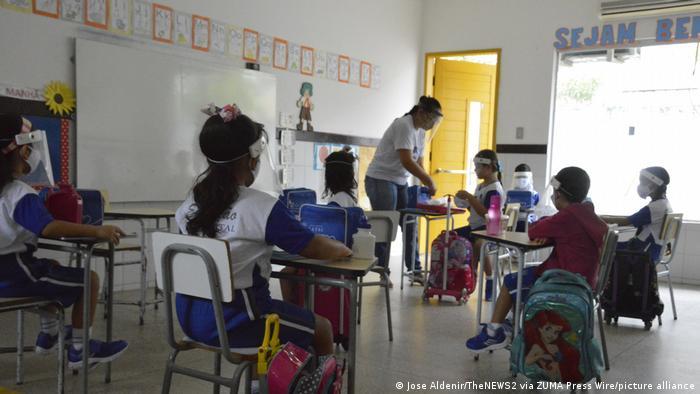 Crianças e professora com proteção facial contra o coronavírus em sala de aula