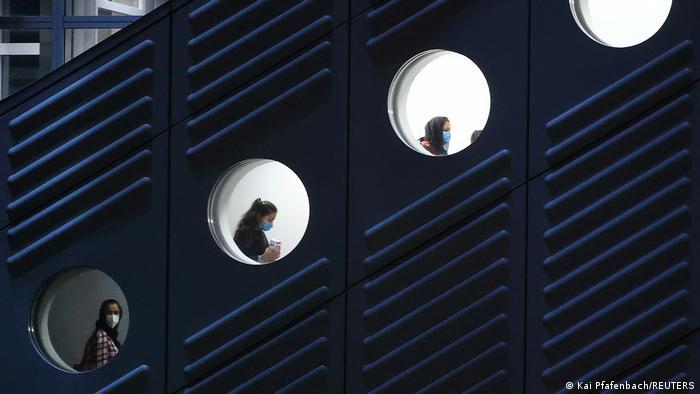 Drei Flüchtlinge mit Masken sind hinter drei Bullaugen beim Aussteigen zu sehen
