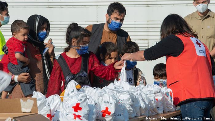 این تصویری است که در ۲۱ اوت در پایگاه نیروی هوایی آمریکا در رامشتاین آلمان گرفته شده است. در این تصویر یکی از کارکنان صلیب سرخ آمریکا را میبینیم که مایحتاج ضروری را در اختیار شهروندانی که از افغانستان گریختهاند قرار میدهد. کودکان در اولویت قرار دارند.