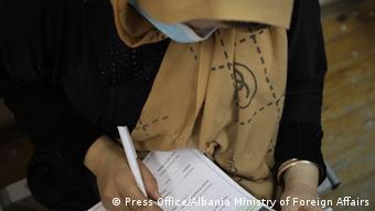 Афганка заполняет документы о предоставлении убежища
