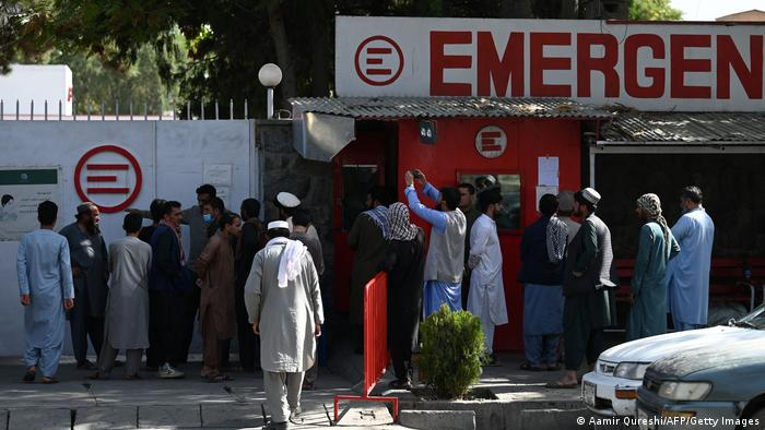 People gather outside a hospital run by Italian NGO Emergency in Kabul after Thursday's deadly attacks