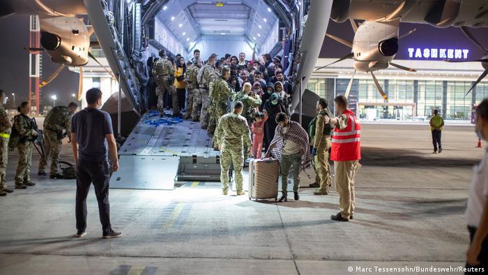 در این عکس که توسط ارتش آلمان در ۲۱ اوت گرفته شده شهروندان افغانستان از یک هواپیمای ترابری ایرباس A400 در تاشکند ازبکستان پیاده میشوند.