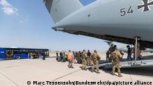 26.08.2021, Taschkent - Schutzbedürftige Menschen gehen kurz nach dem Flug aus Kabul zu einem Bus. Die Bundeswehr hat ihre Evakuierungsmission für Deutsche und einheimische Ortskräfte in Afghanistan am Donnerstagmorgen fortgesetzt. +++ dpa-Bildfunk +++