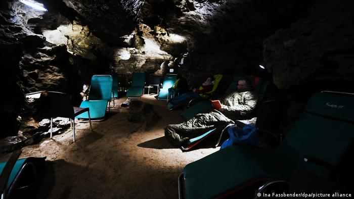 Germany, people sitting in sleeping bags on deck chairs in Klutert Cave