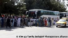 Hundreds of people, some holding documents, gather near an evacuation control checkpoint on the perimeter of the Hamid Karzai International Airport, in Kabul, Afghanistan, Friday, Aug. 27, 2021. (AP Photo/Khwaja Tawfiq Sediqi)