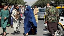 FILE PHOTO: Taliban forces block the roads around the airport, while a woman with Burqa walks passes by, in Kabul, Afghanistan. August 27, 2021. REUTER/Stringer NO RESALES. NO ARCHIVES/File Photo