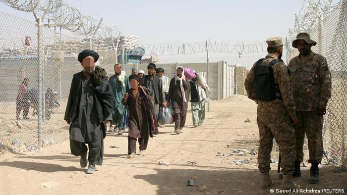 A group of refugees walking alongside a fence