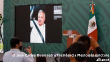 Auf diesem vom mexikanischen Präsidentenamt zur Verfügung gestellten Bild nimmt Andres Manuel Lopez Obrador, Präsident von Mexiko, per Handy an einer Pressekonferenz teil. Demonstrierende Lehrer hatten den Staatschef mehr als zwei Stunden lang nicht aus seinem Wagen aussteigen lassen. (Bestmögliche Qualität.) +++ dpa-Bildfunk +++