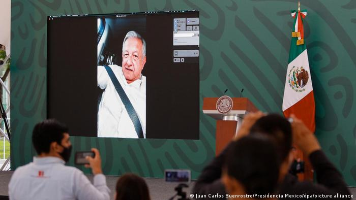 A screen in a conference room shows Lopez Obrador delivering his remarks via video call on his phone from a car