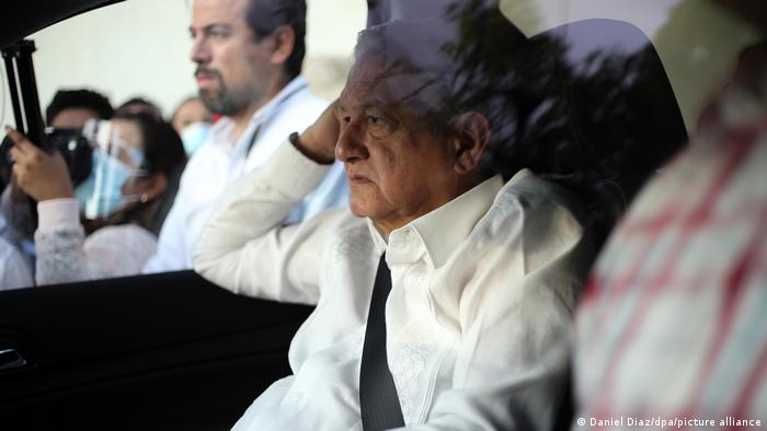 The Mexican president seen in a car with protesters in the background