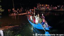 Onlookers gather as others conduct rescue operations for the victims of the boat capsized in Brahmanbaria on August 27, 2021. - At least 19 people were killed and dozens remain missing as a boat packed with passengers and a sand-laden cargo ship collided on August 27 in a lake in eastern Bangladesh, officials said. (Photo by Al Mamun / AFP) (Photo by AL MAMUN/AFP via Getty Images)