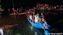 Onlookers gather as others conduct rescue operations for the victims of the boat capsized in Brahmanbaria on August 27, 2021. - At least 19 people were killed and dozens remain missing as a boat packed with passengers and a sand-laden cargo ship collided on August 27 in a lake in eastern Bangladesh, officials said. (Photo by Al Mamun / AFP)
