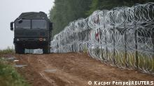 A view of a vehicle next to a fence built by Polish soldiers on the border between Poland and Belarus near the village of Nomiki, Poland August 26, 2021. REUTERS/Kacper Pempel