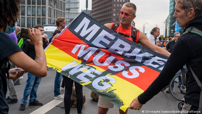 Участник акции протеста в Берлине держит флаг Германии с надписью Меркель должна уйти