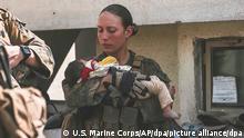 In diesem Bild vom 20. August 2021, das vom US Marine Corps zur Verfügung gestellt wurde, beruhigen Marines der 24. Marine Expeditionary Unit (MEU), darunter Sgt. Nicole Gee (links stehend) Kleinkinder während einer Evakuierung am Hamid Karzai International Airport in Kabul, Afghanistan. Wie die Behörden am 28. August mitteilten, war Gee aus Sacramento, Kalifornien, eine der Marines, die bei dem Bombenanschlag am Donnerstag auf dem Flughafen getötet wurden. (Wiederholung mit verändertem Bildausschnitt) +++ dpa-Bildfunk +++