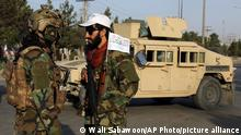 Taliban fighters stand guard at a checkpoint near the gate of Hamid Karzai international Airport in Kabul, Afghanistan, Saturday, Aug. 28, 2021. The Taliban have sealed off Kabul's airport to most would-be evacuees to prevent large crowds from gathering after this week's deadly suicide attack. The massive U.S.-led airlift was winding down Saturday ahead of a U.S. deadline to withdraw from Afghanistan by Tuesday.(AP Photo/Wali Sabawoon)