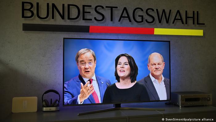 Die Kanzlerkandidaten Armin Laschet, Annalena Baerbock und Olaf Scholz sind nebeneinander auf einem TV-Bildschirm zu sehen, über dem Gerät steht an einer Wand Bundestagswahl.
