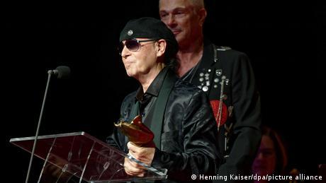 Klaus Meine und Rudolf Schenker stehen an einem Rednerpult, Meine hält eine Auszeichnung in Händen