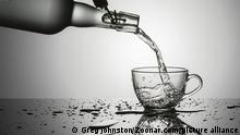 Studio concept image of pouring water from an old glass bottle into a glass cup.
