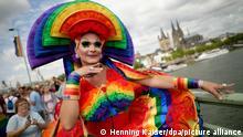 ARCHIV - 07.07.2019, Nordrhein-Westfalen, Köln: Ein Teilnehmer steht bei der Parade zum Christopher Street Day (CSD) vor dem Dom. Am 27.08. beginnt am Abend das Kölner CSD-Wochenende mit dem Bühnenprogramm im «CSD-Veedel». Foto: Henning Kaiser/dpa +++ dpa-Bildfunk +++