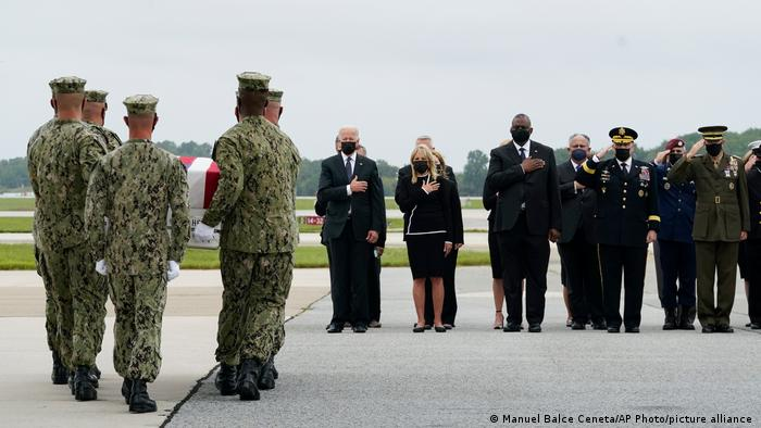 President Joe Biden watches as a Navy carry team moves a transfer case containing the remains of Navy Corpsman Maxton W. Soviak, 22, of Berlin Heights, Ohio