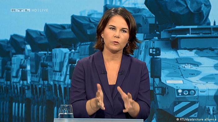 Annalena Baerbock, im Hintergrund Bundeswehrfahrzeuge