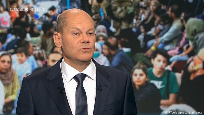 Olaf Scholz im Anzug, im Hintergrund afghanische Flüchtlinge