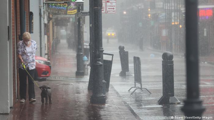 Woman walking her dog in the rain.