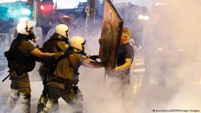 Griechenland   Proteste von Impfgegnern in Athen - EIn Mann wehrt sich mit einer Ikone gegen drei Polizisten