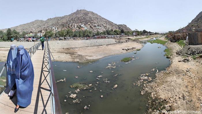 Dos mujeres con chador cruzan un puente sobre un río seco en Kabul.