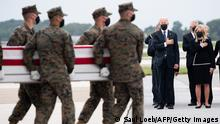 US President Joe Biden(C) attends the dignified transfer of the remains of a fallen service member at Dover Air Force Base in Dover, Delaware, August, 29, 2021, one of the 13 members of the US military killed in Afghanistan last week. - President Joe Biden prepared Sunday at a US military base to receive the remains of the 13 American service members killed in an attack in Kabul, a solemn ritual that comes amid fierce criticism of his handling of the Afghanistan crisis. Biden and his wife, Jill, both wearing black and with black face masks, first met far from the cameras with relatives of the dead in a special family center at Dover Air Force Base in Delaware.The base, on the US East Coast about two hours from Washington, is synonymous with the painful return of service members who have fallen in combat. (Photo by SAUL LOEB / AFP) (Photo by SAUL LOEB/AFP via Getty Images)