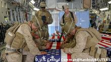 U.S. Marines honor their fallen service members killed in action during a ramp ceremony at Hamid Karzai International Airport in Kabul, Afghanistan August 27, 2021. Picture taken August 27, 2021. U.S. Central Command/Handout via REUTERS THIS IMAGE HAS BEEN SUPPLIED BY A THIRD PARTY.