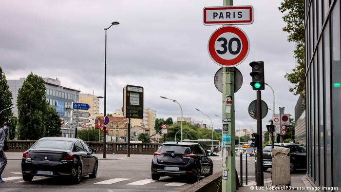 Cars drive by a sign that shows the 30 kph speed limit