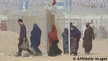Afghan nationals walk along a fenced corridor as they enter Pakistan through the Pakistan-Afghanistan border crossing point in Chaman on August 30, 2021, as dreading another period of harsh rule after the Taliban's rapid takeover following the US troop withdrawal, thousands have been desperately trying to flee Afghanistan. (Photo by - / AFP) (Photo by -/AFP via Getty Images)