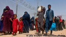 Afghans walk through a security barrier as they enter Pakistan through a common border crossing point in Chaman, Pakistan, Friday, Aug. 27, 2021. Hundreds of Pakistanis and Afghans cross the border daily through Chaman to visit relatives, receive medical treatment and for business-related activities. Pakistani has not placed any curbs on their movement despite recent evacuations from Kabul. (AP Photo/Jafar Khan)