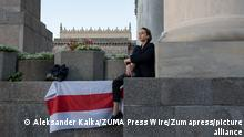 August 9, 2021, Warsaw, Warsaw, Poland: A woman sits next to a historical white-red-white Belarusian flag on August 9, 2021 in Warsaw, Poland. Today marks one year since the wave of protests began in Belarus after the allegedly rigged Presidential elections. People from the Belarus diaspora in Poland gathered by the Palace of Culture and Science to show solidarity to the political prisoners, activists and Belarusian citizens and to write letters to their families. (Credit Image: © Aleksander Kalka/ZUMA Press Wire
