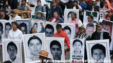 Relatives of the 43 missing students from the Isidro Burgos rural teachers college march holding pictures of their missing loved ones during a protest in Mexico City, Friday, Dec. 26, 2014. Protesters marched through the city to mark the third month since the 43 students were taken by municipal police and then handed over to a drug gang to be killed and then the bodies burned, according to the results of the Attorney General's investigation. (AP Photo/Marco Ugarte)