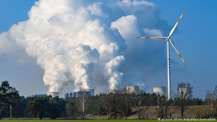 A wind turbine stands in a field in front of a coal-fired power plant in eastern Germany