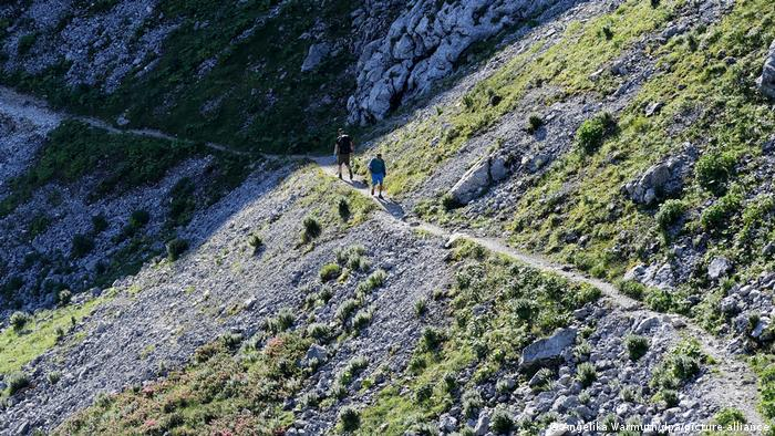 Two people hike on a mountain path