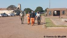 Ndambi Guebuza Ort: Maputo, Mosambik Fotograf: Romeu da Silva, DW Datum: 30.08.2021 Beschreibung: Ndambi Guebuza ist Sohn des ehemaligen Präsidenten Mosambiks, Armando Guebuza. In dessen Amtszeit hat Mosambik mehrere Milliarden US-Dollar illegale Schulden (dívidas ocultas) aufgenommen, die zum großen Teil für Korruptionszahlungen verwendet wurden. Ndambi Guebuza ist einer der Angeklagten in einem Verfahren, das im August in Maputo gegen mutmaßliche Beteiligte an dem Korruptionsskandal stattfand. Das Foto zeigt Ndambi Guebuza auf dem Weg zum Verhandlungssaal (Bildmitte mit dunkler Jacke).