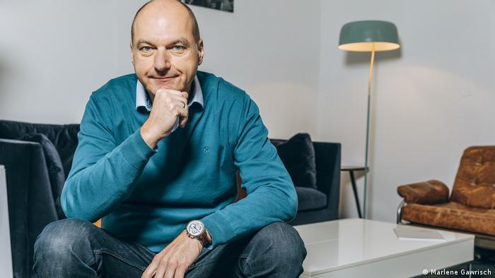 Der Politikberater Frank Stauss sitzt auf einem Tisch vor einem Sofa und stützt das Kinn auf die Hand