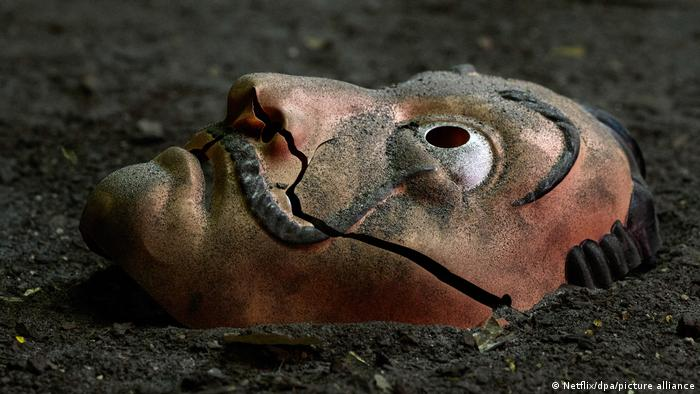 A mask resembling the face of artist Salvador Dalí lays on the ground.
