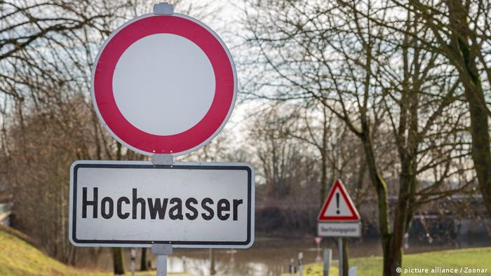 A sign indicating flooding in Germany in front of a body of water