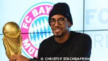 Bayern Munich's defender Jerome Boateng poses with a dummy of the soccer World Cup trophy during an autograph session in the so-called Bayern Munich Erlebniswelt at the stadium in Munich, southern Germany, on March 6, 2016. The defender of Bayern Munich Jerome Boateng is currently injured. / AFP / CHRISTOF STACHE (Photo credit should read CHRISTOF STACHE/AFP via Getty Images)