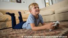 Boy playing video game in the living room at home || Modellfreigabe vorhanden