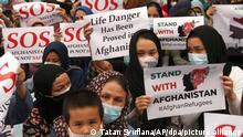 Afghan refugees living in Indonesia hold posters during a rally outside the building that houses UNHCR representative office in Jakarta, Indonesia, Tuesday, Aug. 24, 2021. The protesters, mostly members of the Hazara ethnic minority, held the rally on Tuesday decrying the Taliban's takeover of their country and calling for resettlement in third countries. (AP Photo/Tatan Syuflana)